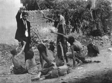 Turkish official teases starving Armenian children by showing them a piece of bread during the Armenian Genocide in 1915