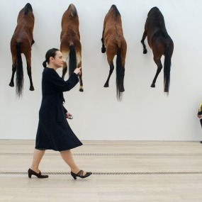 A woman walks past an art project by Italian artist Maurizio Cattelan at the Beyeler Foundation in Basel on June 10, 2013